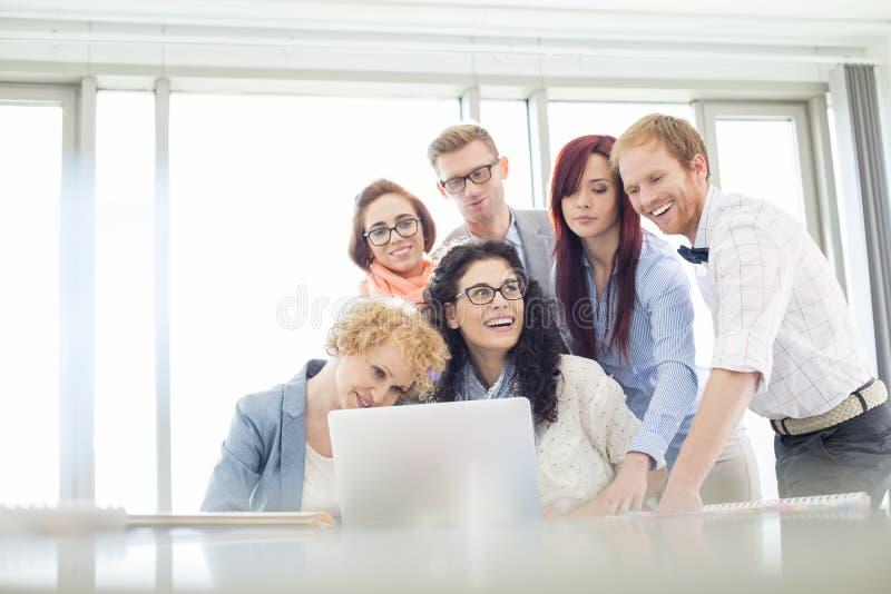 Szczęśliwi biznesowi koledzy dyskutuje w kreatywnie biurze z laptopem obrazy stock