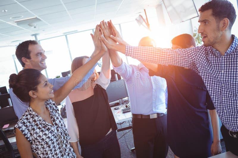 Szczęśliwi biznesowi koledzy stawia ich ręki wpólnie zdjęcie royalty free