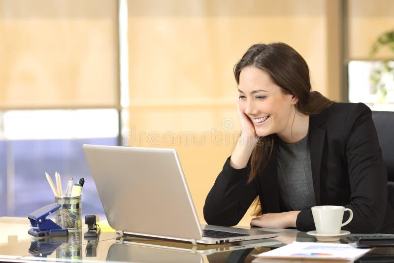 Szczęśliwi bizneswomanu dopatrywania środki w laptopie zdjęcia stock