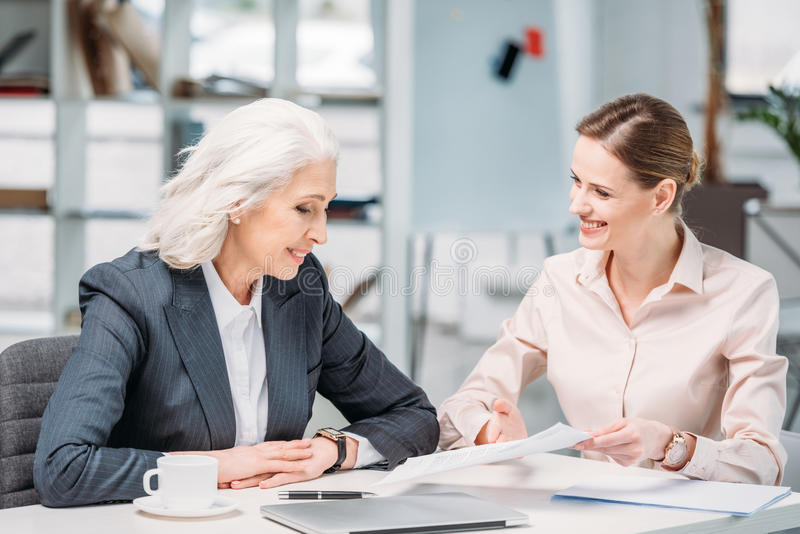 Szczęśliwi bizneswomany dyskutuje biznesowego projekt na spotkaniu w biurze zdjęcia royalty free