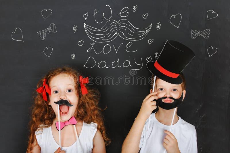 Szczęśliwi bliźniaków dzieciaki trzymają karnawałowego wąsy i brodę, ojca dzień co fotografia stock