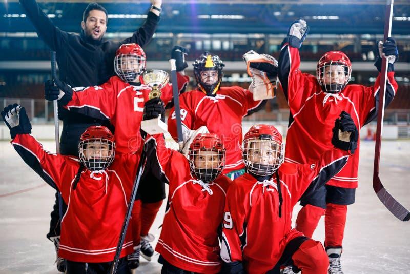 Szczęśliwi chłopiec gracze zespalają się lodowego hokeja zwycięzcy trofeum obraz royalty free