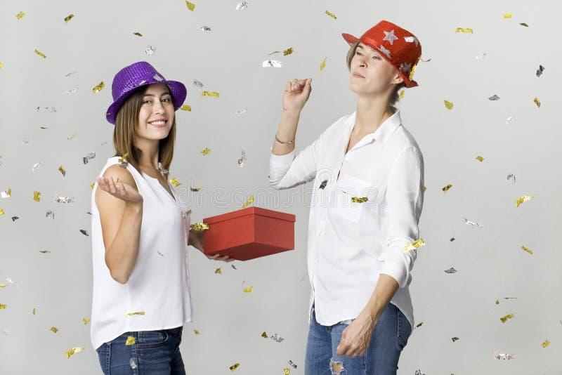 Szczęśliwi dancingowi młodzi żeńscy przyjaciele ono uśmiecha się z prezentem i confetti przeciw białemu tłu odświętność obrazy stock