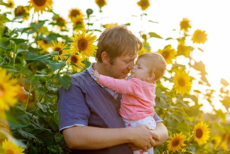 Szczęśliwi dumni potomstwa ojcują z śliczną dziecko córką w słonecznika polu, rodzinny portret wpólnie obraz royalty free