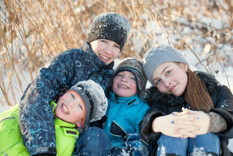 Szczęśliwi dzieci śmia się w winterwear podczas gdy bawić się w snowdrift zdjęcie royalty free