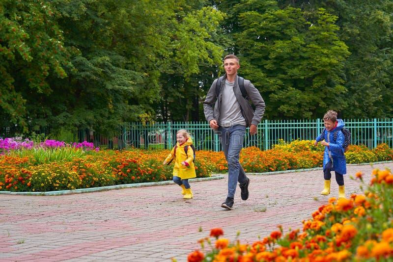 Szczęśliwi dzieci śmiają się szkoła, pośpiech i bieg, ubierająca w deszczowach, z teczką za plecakiem zdjęcia royalty free