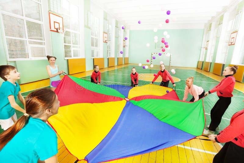 Szczęśliwi dzieci bawić się spadochronową grę w gym fotografia royalty free