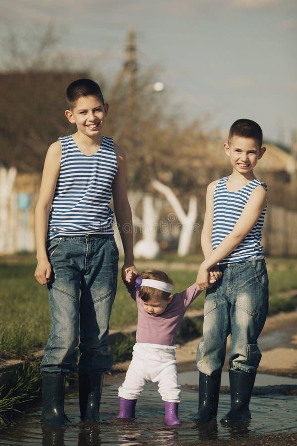 Szczęśliwi dzieci bawić się w kałuży fotografia stock