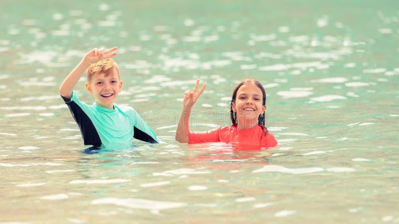 Szczęśliwi dzieci bawić się w morzu, Uśmiecha się dzieciaków ma zabawę w wodzie, wakacje z chłopiec i dziewczyny cieszy się czas, zdjęcie stock