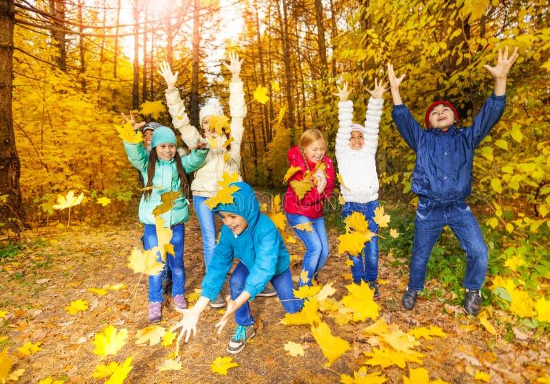 Szczęśliwi dzieci bawić się z latanie liśćmi obraz stock