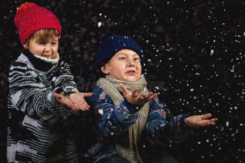 Szczęśliwi dzieci bawić się z płatkami śniegu na zima spacerze obrazy royalty free
