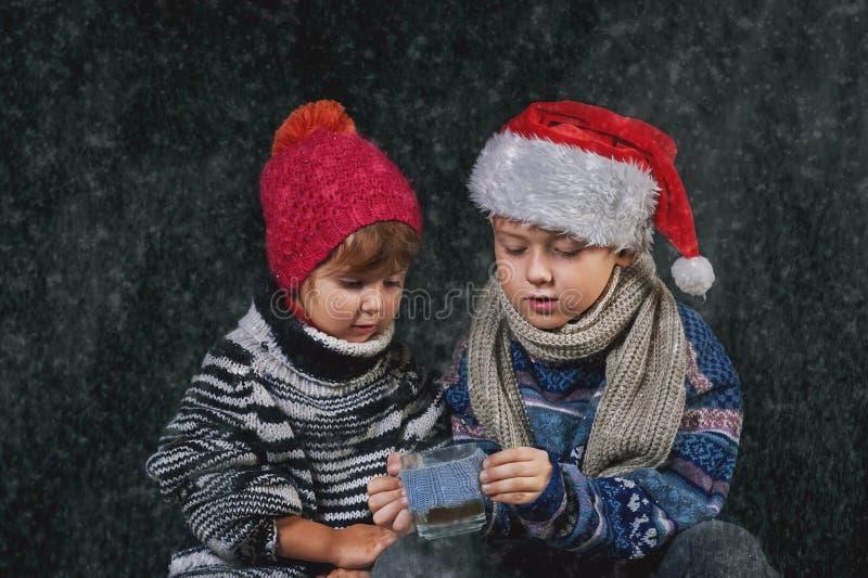Szczęśliwi dzieci bawić się z płatkami śniegu na zima spacerze obraz stock