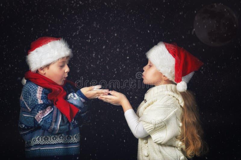 Szczęśliwi dzieci bawić się z płatkami śniegu na zima spacerze obrazy stock