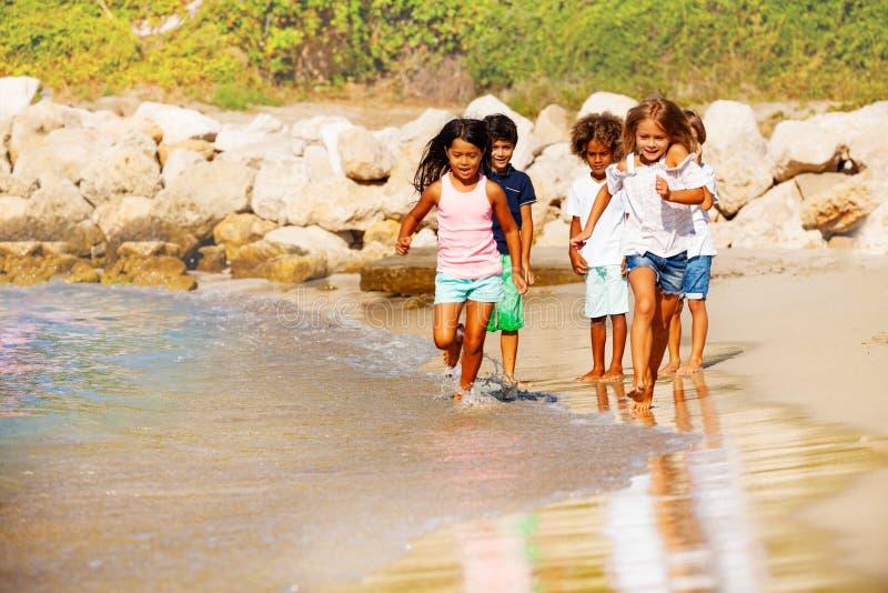 Szczęśliwi dzieci biega na plaży w lecie obrazy royalty free