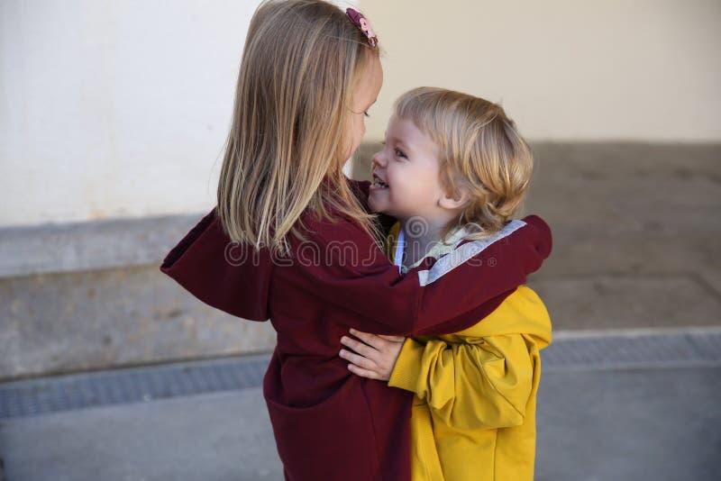 Szczęśliwi dzieci chłopiec i dziewczyna ubierali w hoodie cuddle, pokazuje miłości dla each inny zdjęcia royalty free