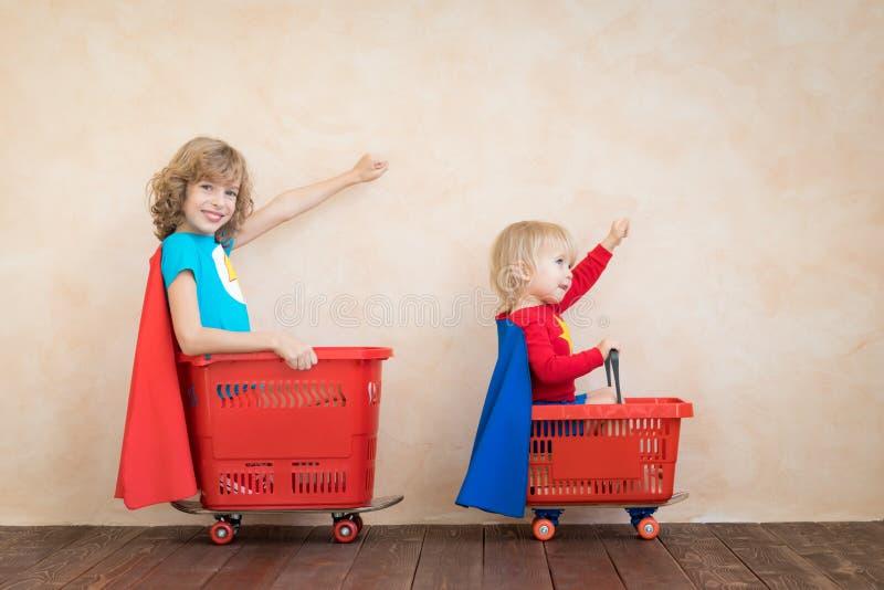 Szczęśliwi dzieci jedzie zabawkarskiego samochód w domu fotografia stock