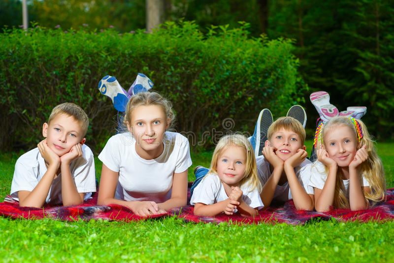 Szczęśliwi dzieci kłama na zielonej trawie outdoors wewnątrz fotografia stock