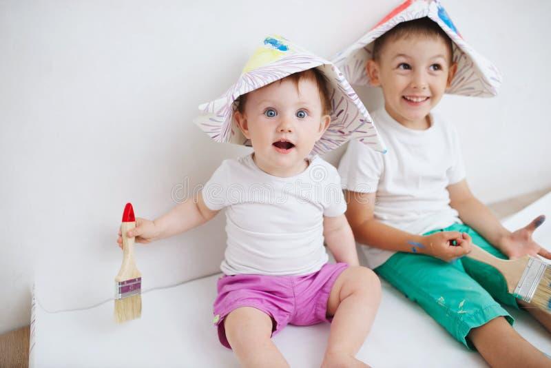 Szczęśliwi dzieci maluje ścianę w domu fotografia stock