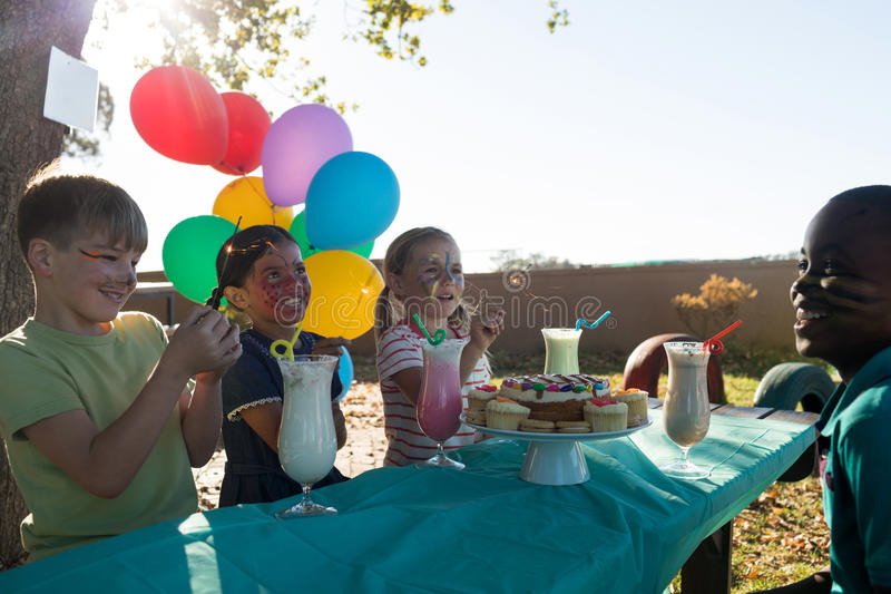 Szczęśliwi dzieci opowiada podczas gdy mieć jedzenie i napoje przeciw niebu przy stołem zdjęcie stock