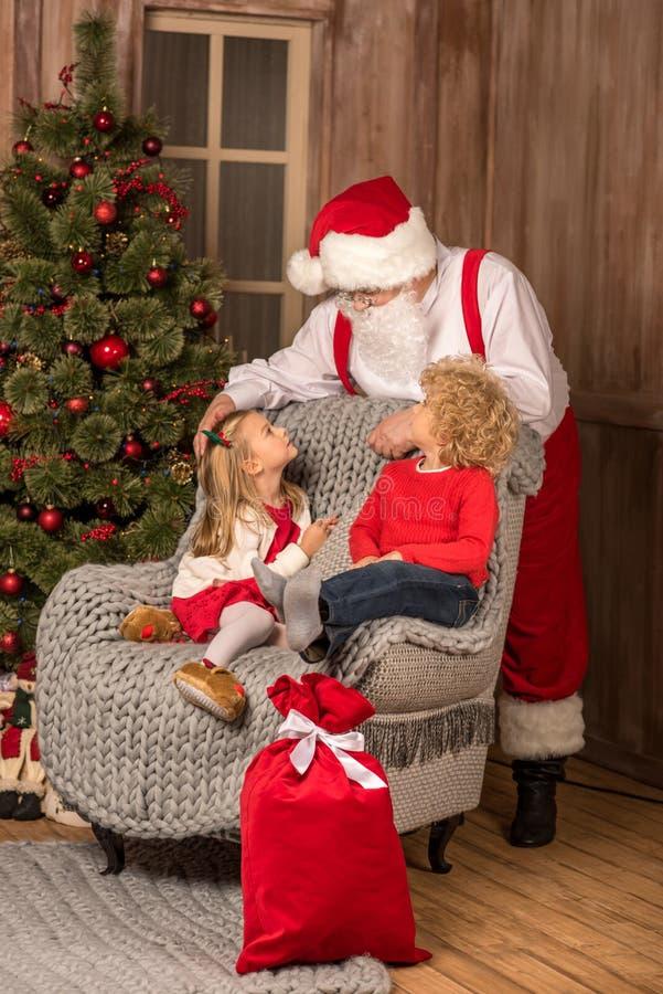 Szczęśliwi dzieci patrzeje Święty Mikołaj fotografia stock
