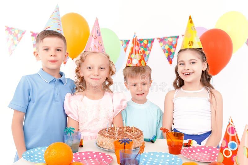 Download Szczęśliwi Dzieci Pozuje Z Urodzinowym Tortem Obraz Stock - Obraz złożonej z róg, tort: 57667585