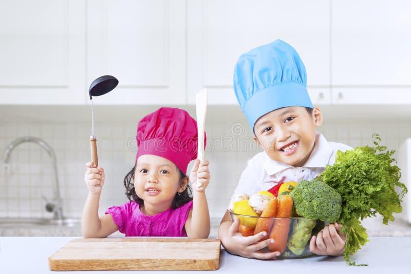 Szefów kuchni dzieci kucbarski warzywo w domu obrazy royalty free