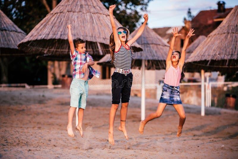 Szczęśliwi dzieci skacze na piaskowatej plaży obraz stock