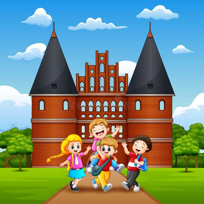 Szczęśliwi dzieci w wieku szkolnym radośni i śmiają się przed Holstentor royalty ilustracja