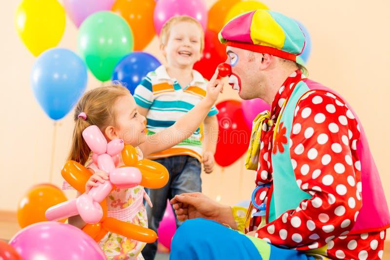 Szczęśliwi dzieci z błazenem na przyjęciu urodzinowym obraz royalty free