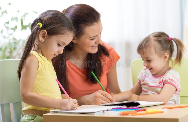 Szczęśliwi dzieci z nauczyciela rysunkiem w sala lekcyjnej obraz stock