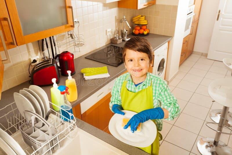Szczęśliwi dzieciak chłopiec domycia naczynia w domowej kuchni fotografia royalty free