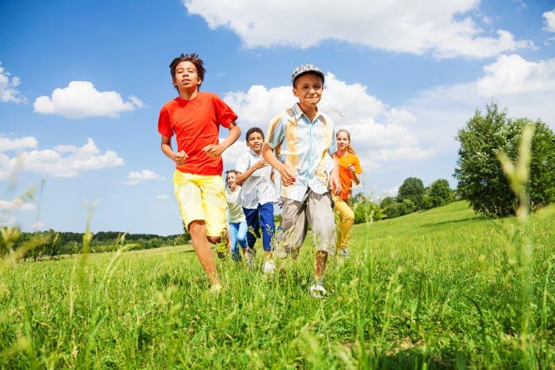 Szczęśliwi dzieciaki bawić się i biegają outside podczas lata obrazy stock