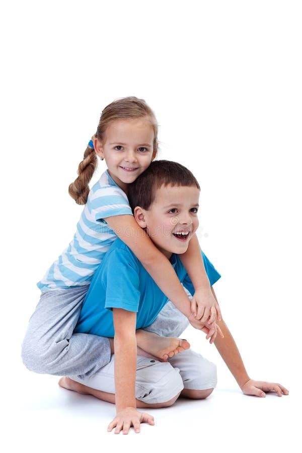 Szczęśliwi dzieciaki bawić się i mocuje się na podłoga obraz stock