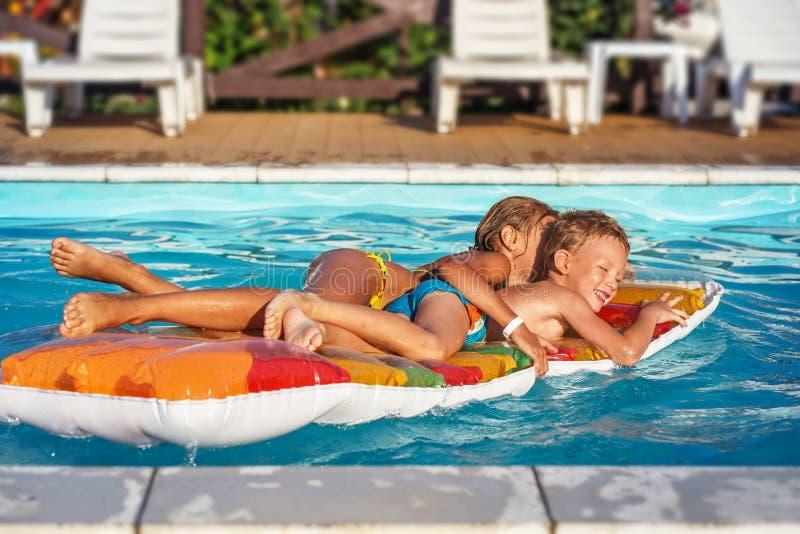 Szczęśliwi dzieciaki bawić się w błękitne wody pływacki basen fotografia stock