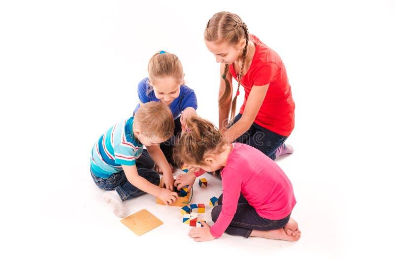 Szczęśliwi dzieciaki bawić się z elementami odizolowywającymi na bielu zdjęcie stock