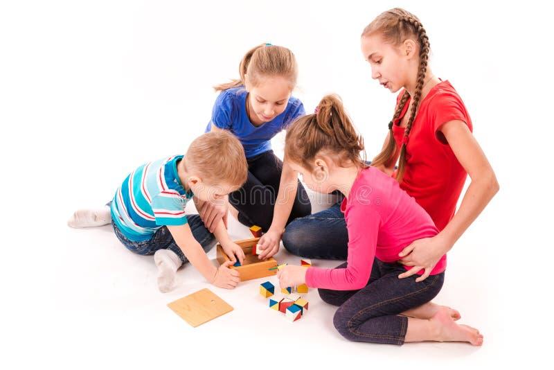Szczęśliwi dzieciaki bawić się z elementami odizolowywającymi na bielu obraz royalty free