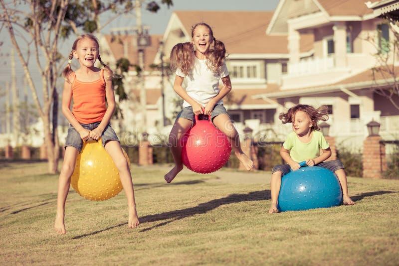 Szczęśliwi dzieciaki bawić się z nadmuchiwanymi piłkami na gazonie zdjęcie stock