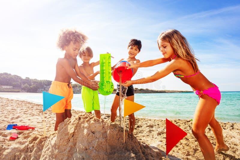 Szczęśliwi dzieciaki bawić się z wodą i piaskiem na plaży obrazy royalty free