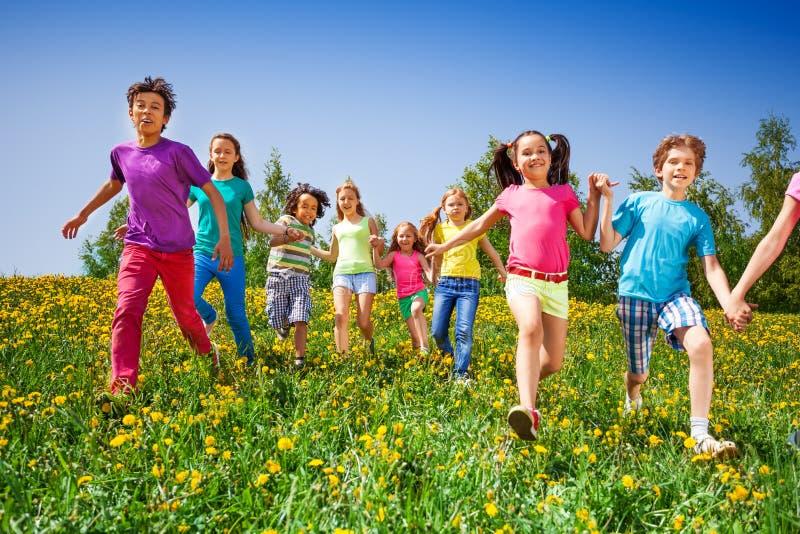 Szczęśliwi dzieciaki bieg i chwyt ręki w zielonej łące fotografia stock
