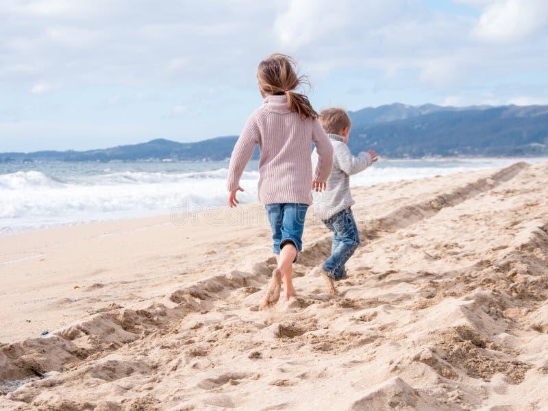 Szczęśliwi dzieciaki biega na plaży na wakacje obraz stock