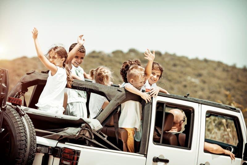 Szczęśliwi dzieciaki cieszy się wycieczkę samochodową obraz royalty free