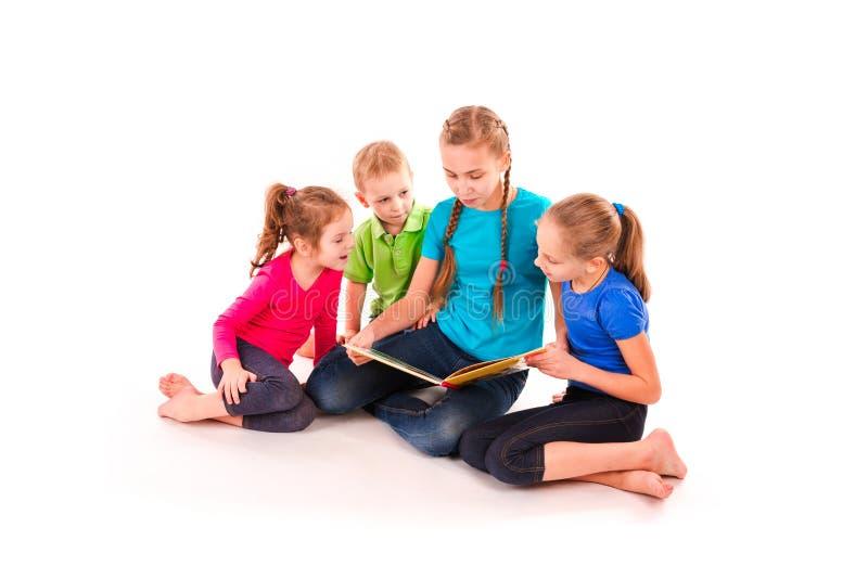 Szczęśliwi dzieciaki czyta książkę na bielu zdjęcia royalty free