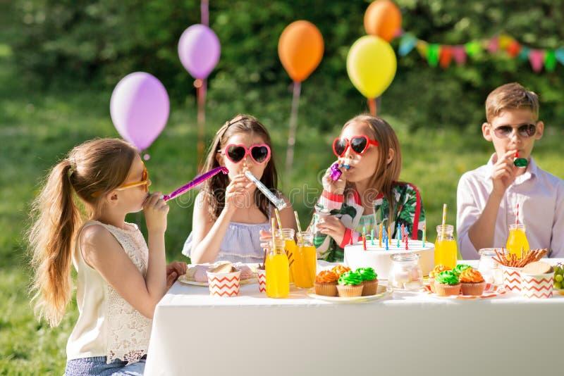 Szczęśliwi dzieciaki dmucha przyjęcia uzbrajać w rogi przy lato urodziny obrazy stock