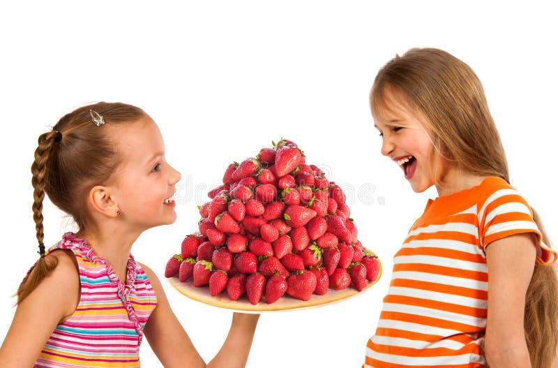 Szczęśliwi dzieciaki je smakowite dojrzałe truskawki obraz royalty free