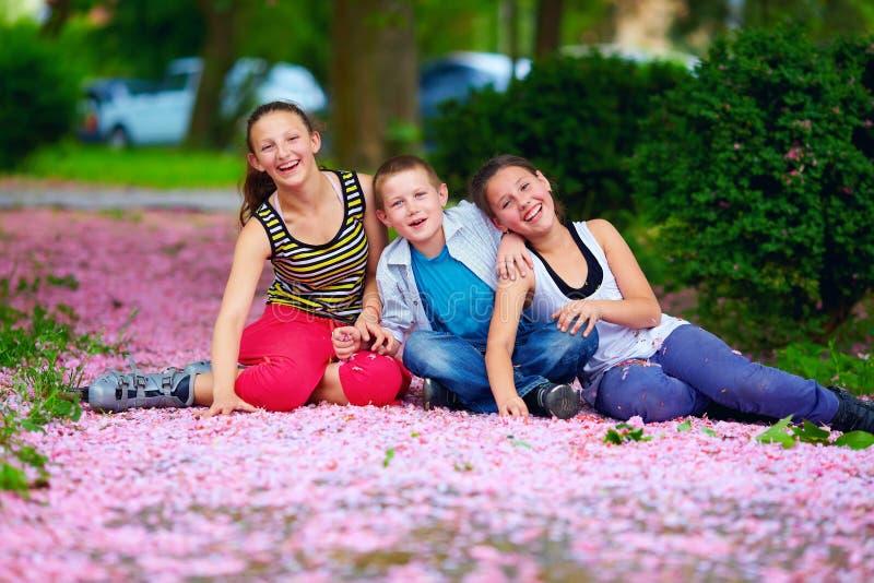 Szczęśliwi dzieciaki, nastolatkowie ma zabawę w kwitnienie parku zdjęcia royalty free