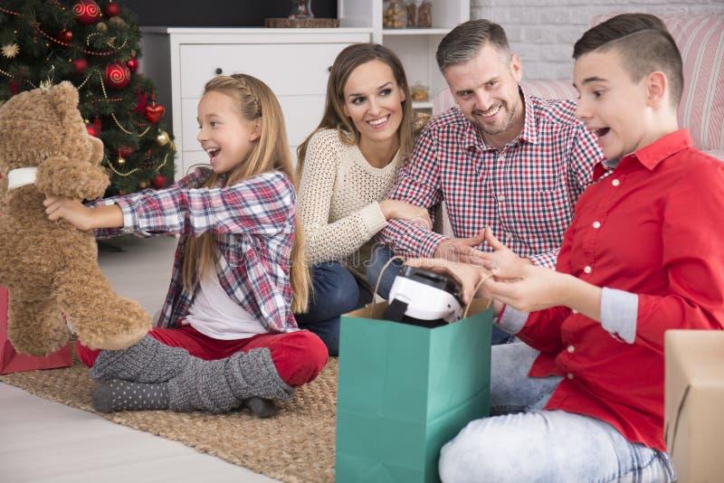 Szczęśliwi dzieciaki odpakowywa boże narodzenie prezenty obraz royalty free