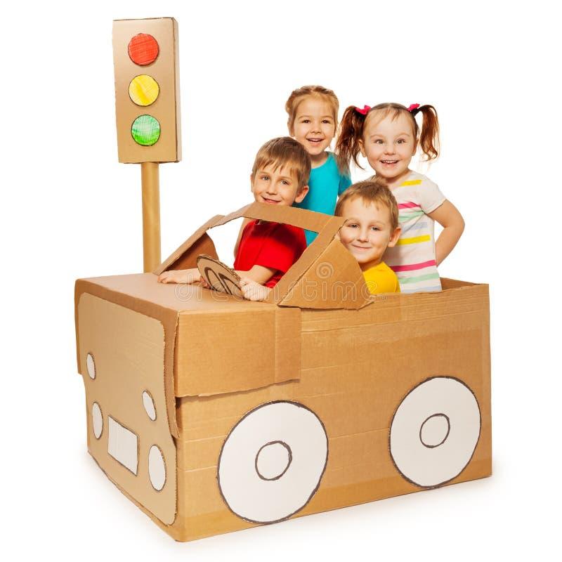Szczęśliwi dzieciaki podróżuje kartonowym samochodem zdjęcia stock