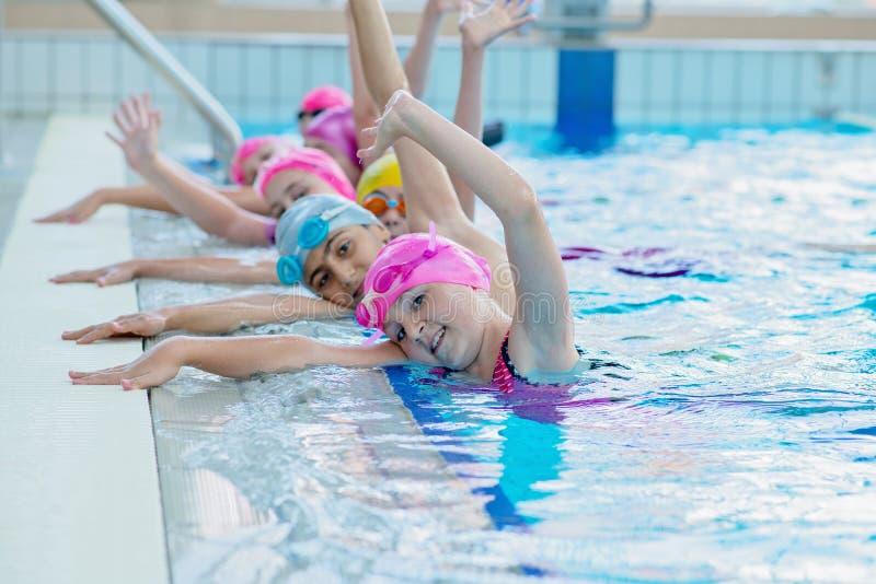 Szczęśliwi dzieciaki przy pływackim basenem Młoda i pomyślna pływaczki poza obrazy stock