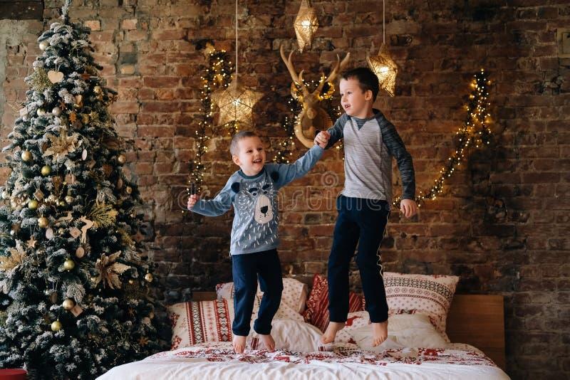 Szczęśliwi dzieciaki skacze na łóżku fotografia stock