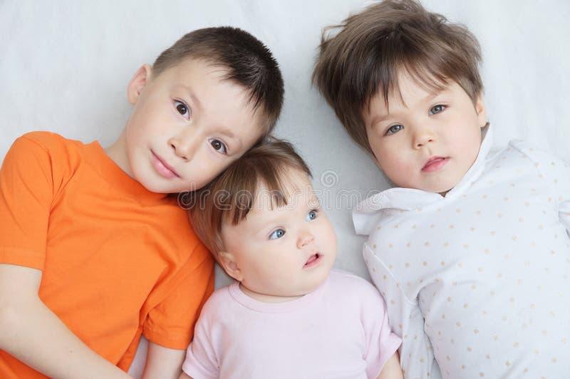 Szczęśliwi dzieciaki, trzy dziecko różnego wieka, portret chłopiec, mała dziewczynka i dziewczynka, kłama, szczęście w dzieciństw zdjęcia stock